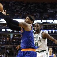 Photo - New York Knicks' Carmelo Anthony grabs a pass over Boston Celtics' Jeff Green (8) during the second quarter of Game 3 of a first round NBA basketball playoff series, Friday, April 26, 2013, in Boston. (AP Photo/Winslow Townson)