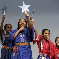 Photo -  Eva Allen, 11, front, and her group, the Bureau of Indian Education Children's Language Class from Carnegie, perform during the Oklahoma Native American Youth Language Fair on Tuesday at the Sam Noble Oklahoma Museum of Natural History. PHOTO BY STEVE SISNEY, THE OKLAHOMAN   STEVE SISNEY -