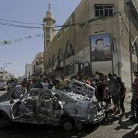 Photo - Palestinians gather around the wreckage of a vehicle following an Israeli airstrike in Gaza City, northern Gaza Strip, Monday, Aug. 25, 2014. Several Palestinians were killed and several more were wounded in an airstrike on the car, according Gaza health official Ashraf al-Kidra. (AP Photo/Adel Hana)