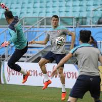 Photo - Portugal's Cristiano Ronaldo, center, challenges for the ball with teammates during an official training session the day before the group G World Cup soccer match between Germany and Portugal at the Arena Fonte Nova in Salvador, Brazil, Sunday, June 15, 2014.  (AP Photo/Paulo Duarte)