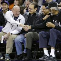 Photo - FILE - In this Jan. 25, 2014, photo, then-Microsoft CEO Steve Ballmer, left, shakes hands with former NBA players Bill Russell, right, and