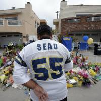 Photo -   San Diego Chargers fan Jerry Lopez looks over a memorial set-up in the driveway of the house of former NFL star Junior Seau Thursday, May 3, 2012, in Oceanside, Calif. Seau's apparent suicide stunned an entire city and saddened former teammates who recalled the former NFL star's ferocious tackles and habit of calling everybody around him