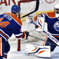 Photo - St. Louis Blues' T.J. Oshie (74) and Edmonton Oilers' Corey Potter (44) look for the rebound as Oilers goalie Ilya Bryzgalov (80) makes the save during the second period of an NHL hockey game in Edmonton, Alberta, on Saturday, Dec. 21, 2013. (AP Photo/The Canadian Press, Jason Franson)