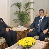 Photo -   In this photo released by the Egyptian Presidency, President Mohammed Morsi, right, poses for a photograph with his new Prosecutor General, Talaat Abdullah, left, in Cairo, Egypt, Thursday, Nov. 22, 2012. Egypt's president on Thursday issued constitutional amendments granting himself far-reaching powers and ordering the retrial of leaders of Hosni Mubarak's regime for the killing of protesters in last year's uprising. Morsi also on Thursday fired the country's top prosecutor by decreeing with immediate effect that he could only stay in office for four years and replacing him with Talaat Abdullah. Morsi fired Abdel-Maguid Mahmoud for the first time in October, but had to rescind his decision when he found that the powers of his office do not empower him to do so. (AP Photo/Egyptian Presidency)