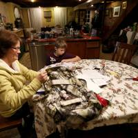 Photo - In this Thursday, Jan. 17, 2013 photo, Irene Sobolov, left, sits at a table while her 10-year-old son Joey Sobolov works on his fifth grade science homework in their home,  in Hoboken, N.J. The living and dining rooms of the Sobolov's home, which are below ground in the basement of their home, were damaged in the floods caused by Superstorm Sandy. Many people in Hoboken, Jersey City and Manhattan who live or have businesses in garden-level buildings have had their flood insurance claims denied, because full coverage does not extend to structures that are underground. Home and business owners are now eligible for grant money under the federal Sandy relief bill, but some are calling for the national flood insurance rules to be changed, saying they are unfair to urban areas. (AP Photo/Julio Cortez)