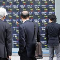 Photo - People watch an electronic stock board of a securities firm in Tokyo, Wednesday, April 8, 2013. Japan's Nikkei 225 index rose 105.45 points to 14,285.69 Wednesday as Asian stock markets were powered higher by an improvement in China's trade and yet another record-busting session on Wall Street. (AP Photo/Koji Sasahara)