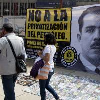 Photo - People walk past a banner that shows an image of the late Mexican President Lazaro Cardenas with a message that reads in Spanish;