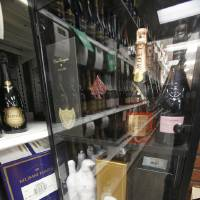 Photo - High-end bottles of Champagne, some costing upwards of $250 a bottle, await customers at Byron's Liquor Warehouse.
