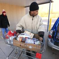 Photo - Food pantry client Sherman Rose loads a basket of food into a vehicle at the BritVil Community Food Pantry.    PHOTO BY PAUL B. SOUTHERLAND, THE OKLAHOMAN  PAUL B. SOUTHERLAND - PAUL B. SOUTHERLAND