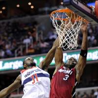 Photo - Miami Heat guard Dwyane Wade (3) goes to the basket against Washington Wizards forward Chris Singleton (31) during the first half of an NBA basketball game, Tuesday, Dec. 4, 2012, in Washington. (AP Photo/Nick Wass)