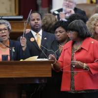 Photo - Rep. Senfronia Thompson, D-Houston, second from left, holds a coat hangar as she stands with fellow representatives while proposing an amendment to the second reading of HB 2, legislation that will restrict abortion rights, on the Texas House floor,Tuesday, July 9, 2013, in Austin, Texas. The Texas House is expected to vote on the bill Tuesday. (AP Photo/Eric Gay)