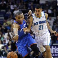 Photo - Oklahoma City Thunder guard Russell Westbrook (0) steals the ball from New Orleans Hornets guard Greivis Vasquez (21) as Vasquez fouls him in the first half of an NBA basketball game in New Orleans, Saturday, Dec. 1, 2012. (AP Photo/gerald herbert)