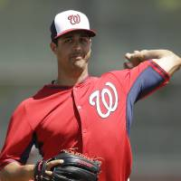 Photo - Washington Nationals starting pitcher Gio Gonzalez warms up before a spring exhibition baseball game against the Houston Astros in Kissimmee, Fla., Sunday, March 16, 2014. (AP Photo/Carlos Osorio)