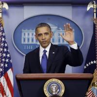 Photo - President Barack Obama waves as he leaves the podium after speaking about the fiscal cliff in the Brady Press Briefing Room at the White House in Washington, Friday, Dec. 21, 2012. (AP Photo/Charles Dharapak)