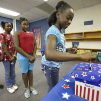 Photo - Fifth-grade students from left, Jennifer Nguyen, Semya Phanor, Napieria Murphy and Alexa Johnson, vote in a presidential election at Highland Park Elementary School in Del City on Friday. Photos by Steve Gooch, The Oklahoman