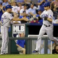 Photo -   Texas Rangers' Josh Hamilton, right, celebrates with third base coach Dave Anderson after hitting a two-run home run during the fourth inning of a baseball game against the Kansas City Royals, Thursday, Sept. 6, 2012, in Kansas City, Mo. (AP Photo/Charlie Riedel)