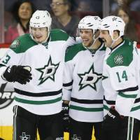 Photo - Dallas Stars' Tyler Seguin, centre, celebrates his goal with teamates Valeri Nichushkin, left, from Russia, and Jamie Benn during third period NHL hockey action against the Calgary Flames in Calgary, Alta., Thursday, Nov. 14, 2013. The Dallas Stars beat the Calgary Flames 7-3. (AP Photo/The Canadian Press, Jeff McIntosh)