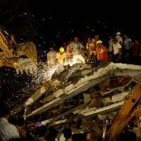 Photo - Rescue workers look for trapped people after a residential building collapsed in Thane, Mumbai, India, Thursday, April 4, 2013. At least 6 persons were killed and 40 were injured when an under-construction residential building collapsed on Thursday evening according to local reports.(AP Photo/Rafiq Maqbool)