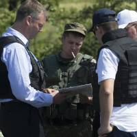 Photo - Alexander Hug, deputy head of the OSCE mission to Ukraine, left, his colleagues and a pro-Russian rebel, 2nd left, examine a map as they try to estimate security conditions outside the city of Donetsk, eastern Ukraine Wednesday, July 30, 2014. (AP Photo/Dmitry Lovetsky)