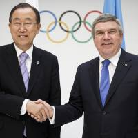 Photo - International Olympic Committee (IOC) president, Thomas Bach, right,  shakes hands with  United Nations (UN) Secretary General, Ban Ki-moon, left, at the IOC Headquarters in Lausanne  Tuesday June 17 2014. The two leaders met to discuss the cooperation between the two organizations. (AP Photo/Keystone, Valentin Flauraud)