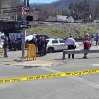 Photo - Law enforcement officers and emergency service personnel converge on the scene of the shooting in downtown Williamson, W.Va., Wednesday, April 3, 2013, where Sheriff Eugene Crum was shot and killed at point blank range. (AP Photo/Williamson Daily News, Kyle Lovern)