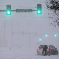 Photo - A Crestwood motorist tries to get his car moving along Watson Road in St. Louis as heavy snow falls on Sunday, Jan. 5, 2014. Snow-covered roads, high winds and ice were creating dangerous driving conditions from Missouri to Delaware on Sunday ahead of a