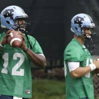 Photo - In this photo taken Friday, Aug. 1, 2014,  North Carolina quarterbacks Marquise Williams (12) and Mitch Trubisky, right, participate in a passing drill during an NCAA  football practice in Chapel Hill, N.C. (AP Photo/Gerry Broome)