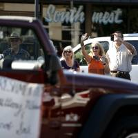Photo - The crowd waves to the homecoming royalty during the Edmond Memorial High School homecoming parade in downtown Edmond. PHOTO BY BRYAN TERRY, THE OKLAHOMAN.  Bryan Terry - THE OKLAHOMAN
