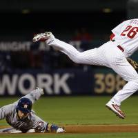 Photo - Philadelphia Phillies second baseman Chase Utley leaps over Houston Astros' Marwin Gonzalez after forcing him out at second on a ball hit by Jake Marisnick during the fourth inning of an interleague baseball game, Thursday, Aug. 7, 2014, in Philadelphia. Marisnick was safe at first on the play. (AP Photo/Matt Slocum)