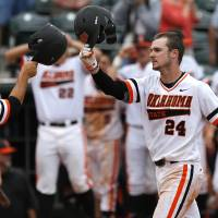 Photo - OSU's Conor Costello celebrates after scoring on a two-run home run in the second inning during a Big 12 Tournament baseball game between Oklahoma State University and the University of Texas at Chickasaw Bricktown Ballpark in Oklahoma City, Saturday, May 24, 2014. Photo by Bryan Terry The Oklahoman