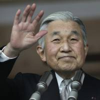 Photo - Japan's Emperor Akihito waves to a crowd of well-wishers through the bulletproof glass of a balcony, during a morning appearance to mark his 79th birthday,  at the Imperial Palace in Tokyo Sunday, Dec. 23, 2012.  (AP Photo/Shizuo Kambayashi)