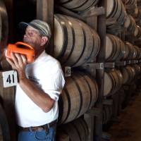 Photo -  In this Sept. 2003 file photo, Dewayne Evans checks for leaks in the barrels of whiskey aging in a warehouse at the George Dickel Distillery near Tullahoma, Tenn. Alcohol regulators ended their investigation Tuesday, June 10, 2014, into whether George Dickel, a subsidiary of liquor giant Diageo, violated state laws by storing whiskey in neighboring Kentucky. (AP Photo/Mark Humphrey, File)   Mark Humphrey -  AP