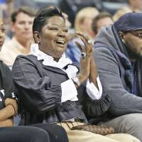 Photo - Wanda Pratt, center, Kevin Durant's mother, applauds as she sits between Tony Durant, right, Kevin's brother, and Kevin's fiancee, Monica Wright, left, during the second quarter of a preseason NBA basketball game as the Oklahoma City Thunder faced the Denver Nuggets in Oklahoma City, Tuesday, Oct. 15, 2013. (AP Photo/Sue Ogrocki)