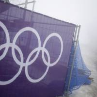 Photo - Security guards walk past the Olympic rings prior to a men's snowboard cross competition at the Rosa Khutor Extreme Park, at the 2014 Winter Olympics, Monday, Feb. 17, 2014, in Krasnaya Polyana, Russia. (AP Photo/Andy Wong)