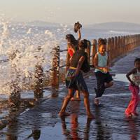 Photo - In this photo taken on Sunday, Aug. 24, 2014, children, right, react as they are sprayed by a wave on the promenade, a popular tourist hotspot near the city of Cape Town, South Africa. This is the perfect vantage point to see arrogant sea gulls, waves crashing onto rocks and miles of Atlantic beaches. With the taste of sea salt in the air, you can walk, jog or sit on a bench to view the Mother City. (AP Photo/Schalk van Zuydam)