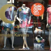 Photo - In this July 12, 2014 photo, Lebanese shoppers are seen reflected, at left, by a shop window that is decorated with the Islamic crescent symbol representing the season of Ramadan, with the words,
