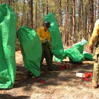 Photo - In this April 12, 2012 photo provided by the Cronkite News, Granite Mountain Hotshots crew members train on setting up emergency fire shelters outside of Prescott, Ariz. On Sunday, June 30, 2013, 19 members of the Prescott-based crew were killed in the deadliest wildfire involving firefighters in the U.S. for at least 30 years. The firefighters were forced to deploy their emergency fire shelters - tent-like structures meant to shield firefighters from flames and heat - when they were caught near the central Arizona town of Yarnell, according to a state forestry spokesman. (AP Photo/Cronkite News, Connor Radnovich)