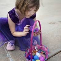 Photo - Lily Rose Botham looks inside an Easter egg Saturday during a hunt at ProCure Proton Therapy Center in  Oklahoma City. Photo by Sarah Phipps, The Oklahoman