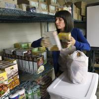 Photo - Amber Dubuc, seventh-grade counselor at Taft Middle School,  grabs food from shelves in the school's