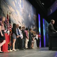 Photo - This May 21, 2014 photo provided by the North Dakota Petroleum Council shows a group of eight-graders from West Fargo's Cheney Middle School standing behind North Dakota Attorney General Wayne Stenehjem as he addresses the Williston Basin Petroleum Conference in Bismarck, N.D. The students were at the conference to present projects addressing problems caused by or related to oil development in the state. (AP Photo/North Dakota Petroleum Council, Renae Mitchell)