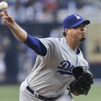 Photo - Los Angeles Dodgers starting pitcher Josh Beckett releases a pitch against the San Diego Padres during the first inning of a baseball game Saturday, June 21, 2014, in San Diego. (AP Photo/Lenny Ignelzi)
