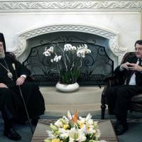 Photo - Cypriot President Nicos Anastasiades, right, meets with Cypriot Archbishop Chrysostomos II at Presidential palace in Nicosia, Wednesday, March 20, 2013.  Following the talks with President Anastasiades,  the head of Cyprus' influential Orthodox church Archbishop Chrysostomos II said on Wednesday that he will put the church's assets at the country's disposal to help pull it out of a financial crisis.  Cypriot lawmakers have rejected a critical draft bill that would have seized part of people's bank deposits in order to qualify for a vital international bailout. (AP Photo/Petros Giannakouris)