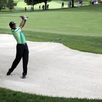 Photo - Tiger Woods chips out of a sand trap on the ninth fairway during the first round of the Quicken Loans National PGA golf tournament, Thursday, June 26, 2014, in Bethesda, Md. (AP Photo/Patrick Semansky)
