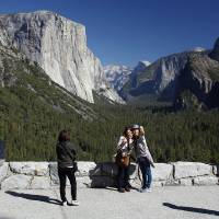 Photo - File - In this Oct. 17, 2013 file photo, visitors at Tunnel View, like Kaori Nishimura and Eriko Kuboi, from Japan, center facing, enjoy the views of Yosemite National Park, Calif. Tunnel View is a scenic vista which shows off El Capitan, Half Dome and Bridalveil Fall. Yosemite National Park is celebrating the 150th anniversary of President Abraham Lincoln's signing of the Yosemite Grant Act, Monday June 30, 2014, which protected Yosemite Valley and Mariposa Grove. (AP Photo/Gary Kazanjian, File)
