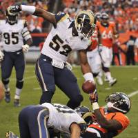 Photo - Denver Broncos running back Ronnie Hillman (21) fumbles the ball as he is hit by St. Louis Rams cornerback Cortland Finnegan (31) in the second quarter of a preseason NFL football game, Saturday, Aug. 24, 2013, in Denver. St. Louis Rams linebacker Alec Ogletree (52) recovered the fumble and ran it back for a touchdown. (AP Photo/Jack Dempsey)
