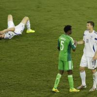 Photo - Bosnia's Edin Dzeko shakes hand with Nigeria's Efe Ambrose as Bosnia's goalkeeper Asmir Avdukic sits on the floor during the group F World Cup soccer match between Nigeria and Bosnia at the Arena Pantanal in Cuiaba, Brazil, Saturday, June 21, 2014. (AP Photo/Fernando Llano)