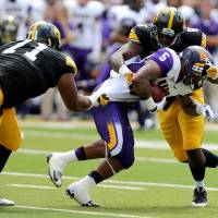 Photo - Iowa defensive lineman Carl Davis (71) and linebacker Reggie Spearman tackle Northern Iowa running back Darrian Miller during the first half of an NCAA college football game, Saturday, Aug. 30, 2014, in Iowa City, Iowa. (AP Photo/Justin Hayworth)