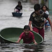 Photo -   A Filipino boy plays along a flooded street in Obando town, Bulacan province, north of Manila, Philippines Tuesday July 31, 2012. Typhoon Saola dumped torrents of rain as it swept past the Philippines, killing at least seven people and displacing more than 20,000 others by Tuesday. (AP Photo/Aaron Favila)