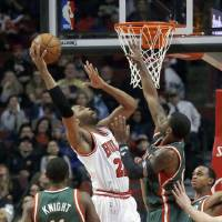 Photo - Chicago Bulls forward Taj Gibson (22) shoots over Milwaukee Bucks shooting guard O.J. Mayo, right, as Brandon Knight (11) watches during the first half of an NBA basketball game Tuesday, Dec. 10, 2013, in Chicago. (AP Photo/Charles Rex Arbogast)