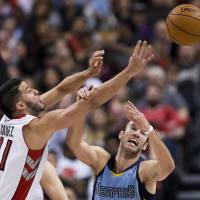 Photo - Toronto Raptors guard Greivis Vasquez, left, battles for the loose ball against Memphis Grizzlies guard Nick Calathes, right, during first half NBA basketball action in Toronto on Friday, March. 14, 2014. (AP Photo/The Canadian Press, Nathan Denette)